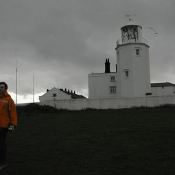 Bloke in Bright Orange Jacket in Front of Lighthouse