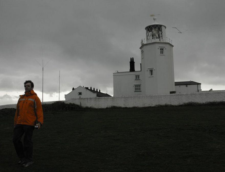 Bloke in Bright Orange Jacket in Front of Lighthouse